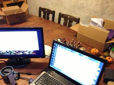 Computer-creative work in process with box of jewelry supplies and sculptures visible behind.