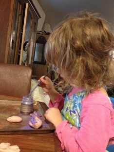 Helping mama put pigment on sculptures.